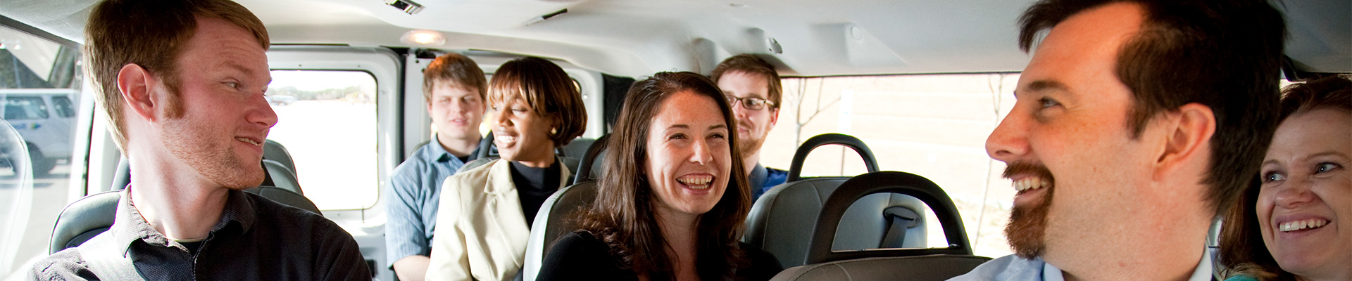 Ridesharing group talking and laughing inside vanpool van